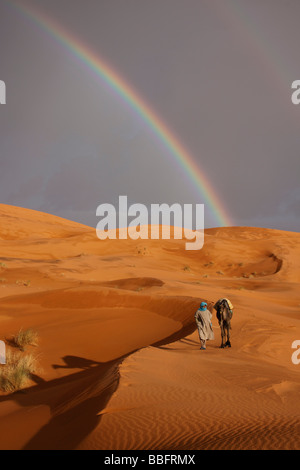 Afrique, Afrique du Nord, Maroc, Sahara, Merzouga, Erg Chebbi, Berbère Tribesman menant Camel, arc-en-ciel dans le désert