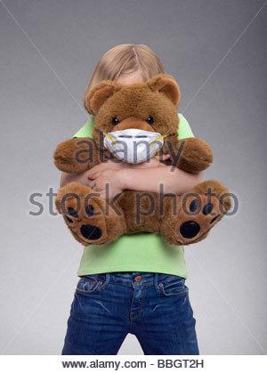 Young Girl lying un ours en peluche portant un masque, studio shot Banque D'Images