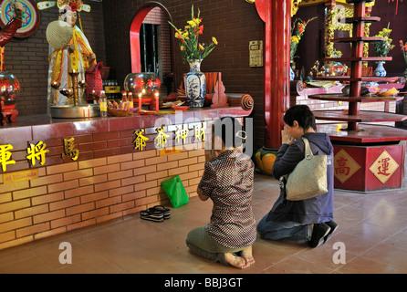 Deux femmes à genoux et priant devant un autel de Bouddha, Quan Am Pagoda, Ho Chi Minh Ville, Saigon, Vietnam, Asie Banque D'Images