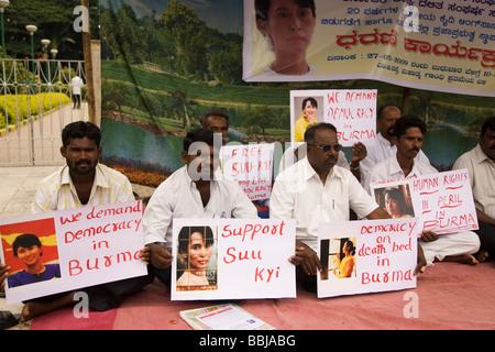 Les hommes tiennent des pancartes au cours d'une manifestation en Inde contre l'absence de démocratie en Birmanie et à l'incarcération et le traitement de Suu Kyi.