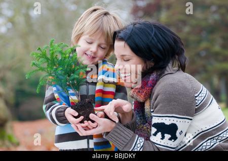La mère et le jeune garçon tenant petit arbre prêt à planter, Vancouver, Colombie-Britannique Banque D'Images