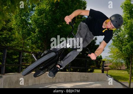 Vélo BMX rider s'envoler un mur en béton de l'air dans un milieu urbain skatepark Toronto Banque D'Images