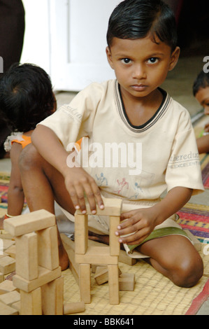 Jeune enfant dans l'un des nombreux bidonvilles de Chennai banlieue crèche; Inde, Tamil Nadu, Chennai (Madras) ...