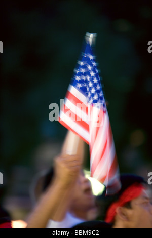 Une main dans une foule agitant un petit drapeau de l'Amérique. Banque D'Images