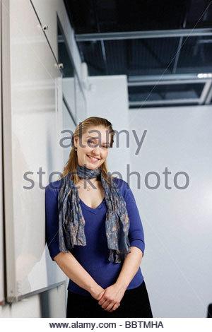 Woman smiling, contre un tableau blanc Banque D'Images