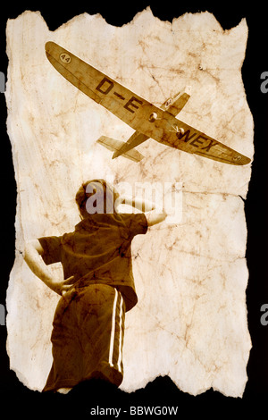 Un jeune garçon regardant un avion voler au-dessus. Banque D'Images