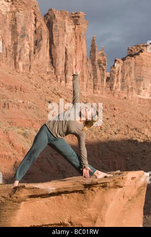 Woman in yoga pose sur grès grès roche en dessous des tours, Moab, Utah. Banque D'Images