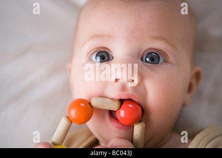 Trois mois baby girl de saisir et de bouche + un anneau de dentition composé de perles en bois, de mâcher sur toy Banque D'Images