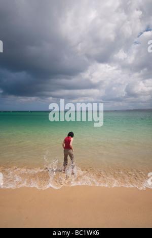 Les femmes sur la plage de Porthminster St Ives en Cornouailles avec de gros nuages sombres s'approchant Banque D'Images
