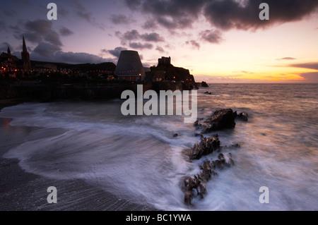 La houle et les vagues le lavage en plus de la plage de la ville au crépuscule à Ilfracombe Devon UK Banque D'Images
