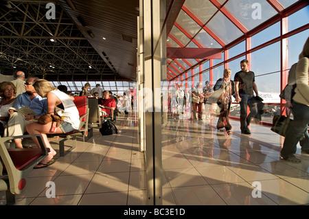 Les passagers au départ et à l'arrivée dans la même scène, séparés par une paroi en verre. L'Aéroport International Banque D'Images
