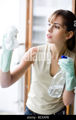 Young woman washing windows Banque D'Images