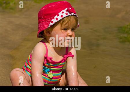 Baby Girl dans un maillot de bain et chapeau rouge et blanc était assis sur la plage de sable Banque D'Images