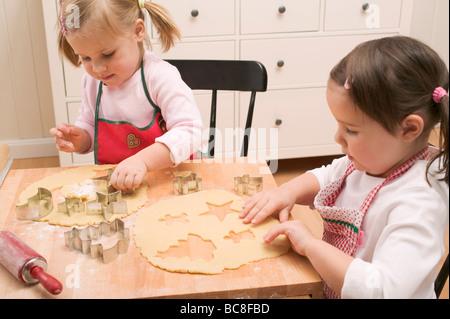 Deux petites filles découper des biscuits - Banque D'Images