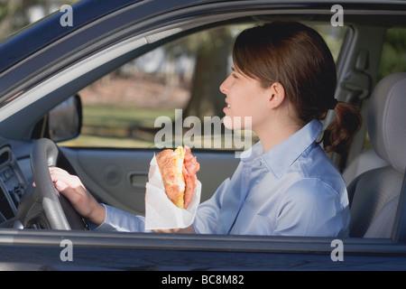 Young woman eating croissant en voiture - Banque D'Images