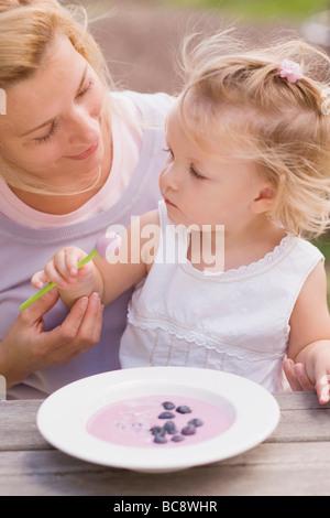 Mère et fille, avec un plat de yogourt aux bleuets - Banque D'Images