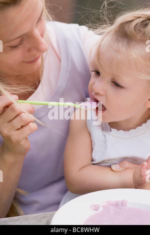L'alimentation de la mère de yogourt aux bleuets - jeune fille Banque D'Images