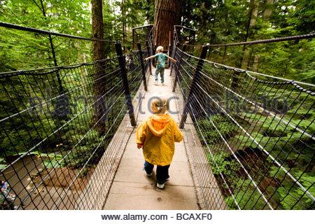 Un frère et une soeur traverser le pont suspendu de Capilano. Banque D'Images