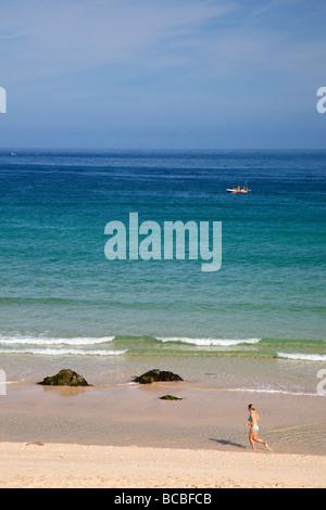Jeune femme femme jogger le jogging sur la plage de Porthmeor avec bateau de pêche en été, St Ives Cornwall England Banque D'Images