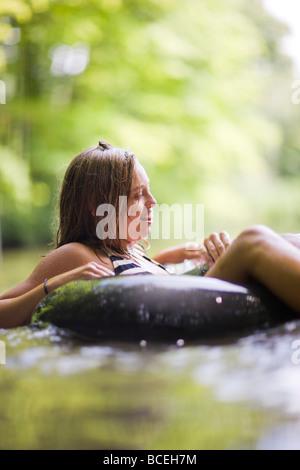 Les adolescents assis dans innertubes dans l'eau Banque D'Images