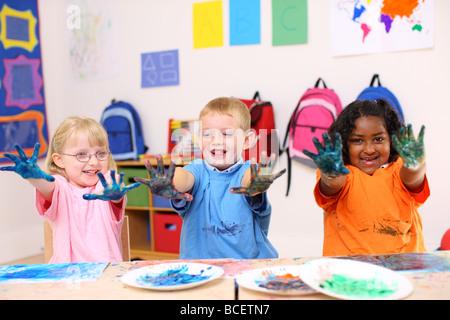 Trois enfants d'âge préscolaire avec les mains couvertes de peinture Banque D'Images