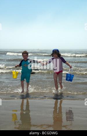 Frère Sœur portant un seaux sur Pendine Beach South Wales UK Banque D'Images