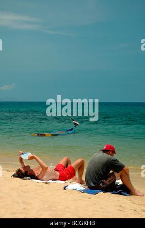 Un couple de touristes pondre sur une plage des Caraïbes. Banque D'Images