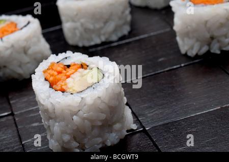 Une faible profondeur horizontale inclinée focus macro de sushi sur un fond en bois noir Banque D'Images