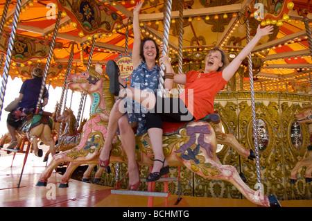 Deux filles sur une journée à Brighton à cheval sur le carrousel sur la plage. Banque D'Images