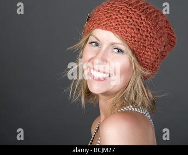 Tiré d'une belle blonde Girl Smiling in Beanie Hat Orange Banque D'Images