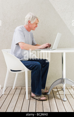 Middle aged man sitting on desk and using laptop Banque D'Images
