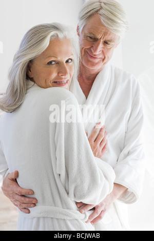 Couple d'âge moyen en peignoirs hugging Banque D'Images