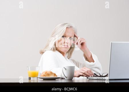 Femme d'âge moyen à l'aide d'ordinateur portable au moment du petit-déjeuner Banque D'Images