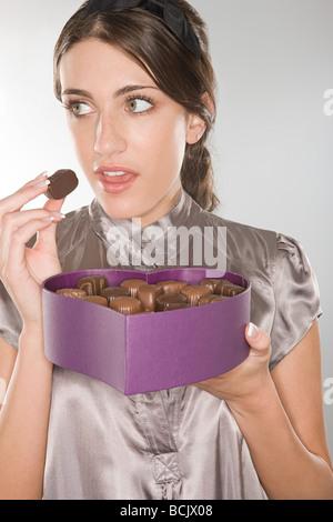 Manger un chocolat femme sournois Banque D'Images