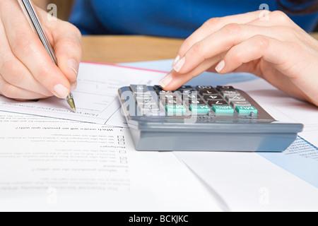 Personne avec la calculatrice et formulaires Banque D'Images