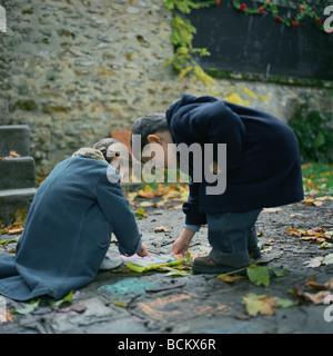 Garçon et fille à la craie sur le sol, à l'extérieur