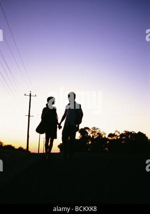 Silhouette de couple holding hands at Twilight