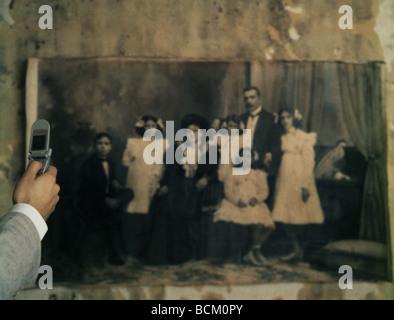 L'homme à l'aide d'un téléphone cellulaire pour la photographie noir et blanc d'une photo de famille sur le mur, Banque D'Images