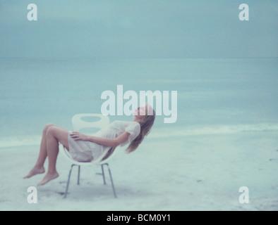Jeune femme couchée sur le côté dans chair on beach, pleine longueur Banque D'Images