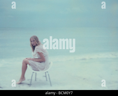 Jeune femme assise dans chair on beach, looking at camera, pleine longueur Banque D'Images