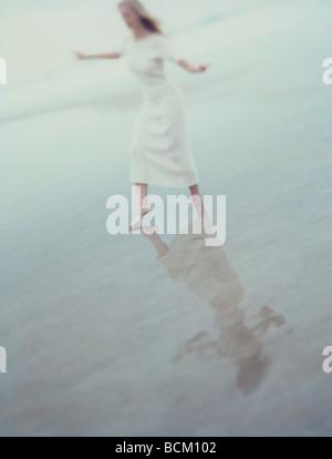 Robe femme en marchant dans l'eau peu profonde à la plage Banque D'Images