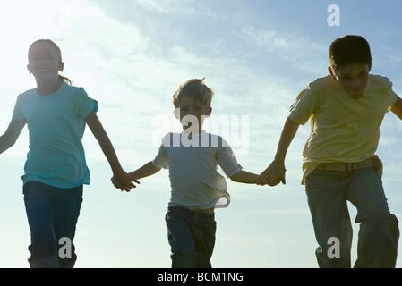 Trois enfants en marche, se tenant la main, rétroéclairé Banque D'Images