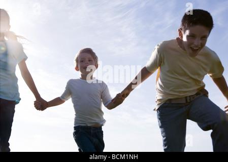 Trois enfants en marche, se tenant la main et riant, low angle view Banque D'Images