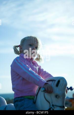 Fille assise sur le cheval à bascule, poignées de maintien, close-up Banque D'Images
