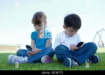 Chaque fille et garçon l'utilisation de téléphones cellulaires, assis sur l'herbe, pleine longueur Banque D'Images