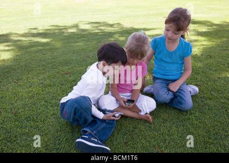 Les enfants utilisant des téléphones cellulaires, assis sur l'herbe, pleine longueur Banque D'Images