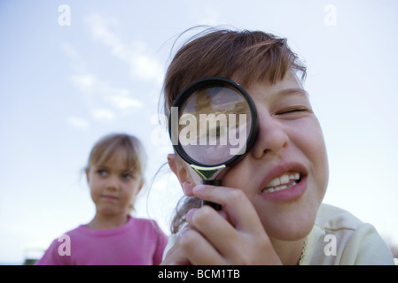 Girl looking through loupe, looking at camera, close-up