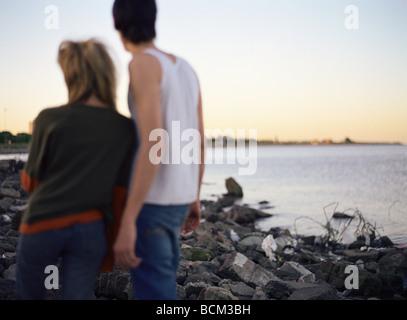 Jeune couple standing on Rocky beach jonchée d'indésirable, à la recherche au coucher du soleil, vue arrière Banque D'Images