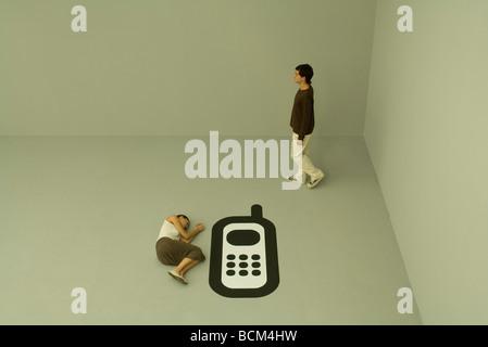 Femme couchée sur le sol à côté de grandes téléphone cellulaire, l'homme marche loin