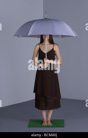 Femme debout sous parapluie sur gazon artificiel, le visage partiellement masqué Banque D'Images